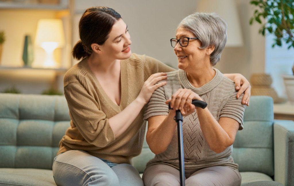 Pflegerin sitzt mit einer älteren Frau auf einer Couch.